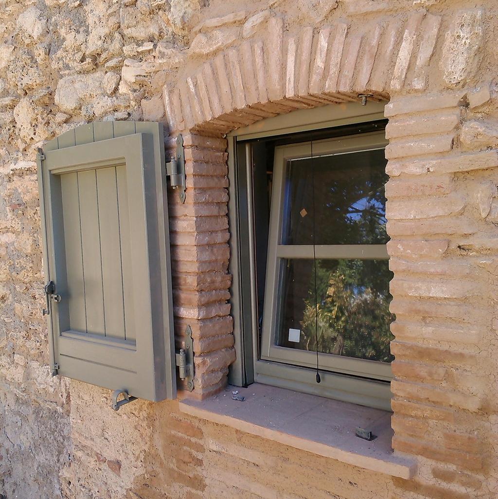 Finestra con traversino orizzontale e sistema di apertura anta-ribalta completa di sportellone centinato in legno di larice laccato